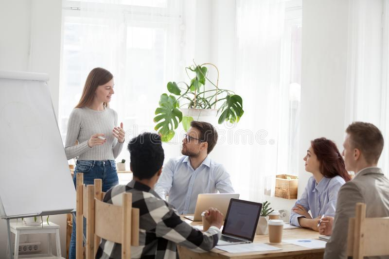 Female mentor give flipchart presentation to diverse workers. Millennial female employee make flipchart presentation for diverse employees during meeting, young stock photos