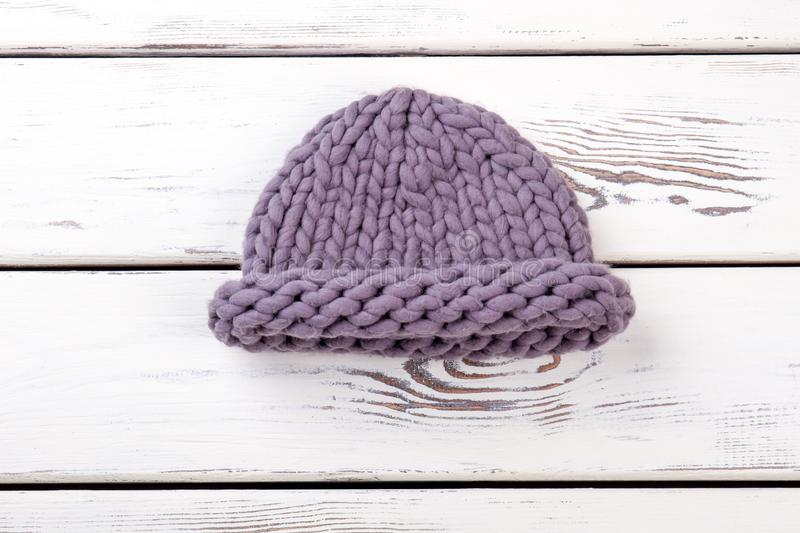 Female merino knitted hat. Women purple color winter hat on white wooden background. Ladies winter fashion accessory stock image