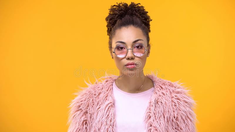 Female millennial in stylish cloth looking in camera on bright background, model royalty free stock image