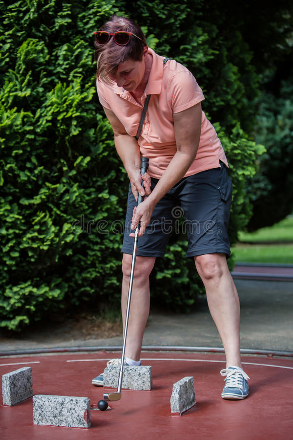 Female minigolf player has some fun to put a black ball into the stock image