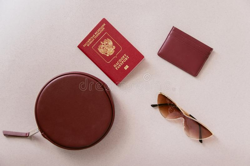 Female minimum travel set. Maroon passport, cardholder and wallet with a bag and glasses on a pastel beige background stock photo