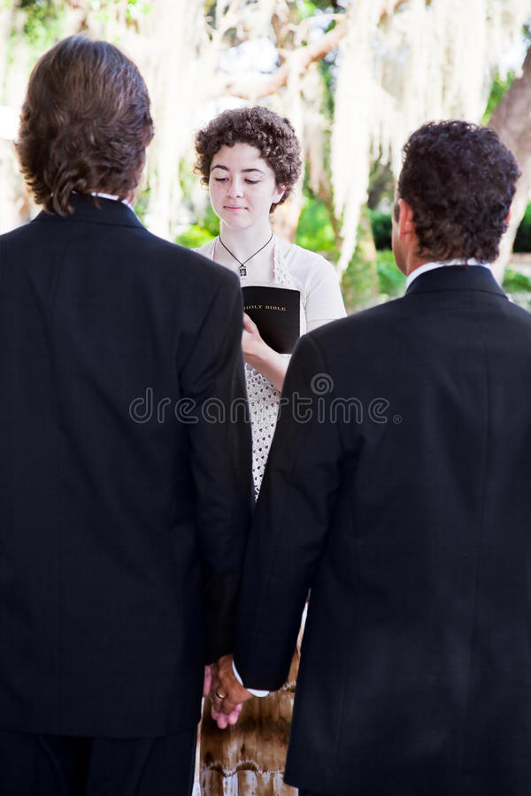 Female Minister Marries Gay Couple. Young female minister marries gay male couple in lovely outdoor wedding ceremony stock photo