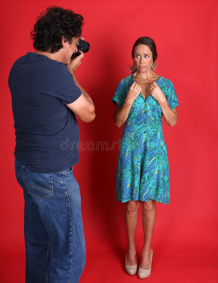 Female model being abused by a Photographer. Actually a mature model and her husband stock image