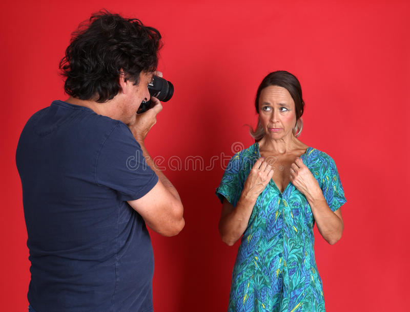 Female model being abused by a Photographer. Actually a mature model and her husband stock photography