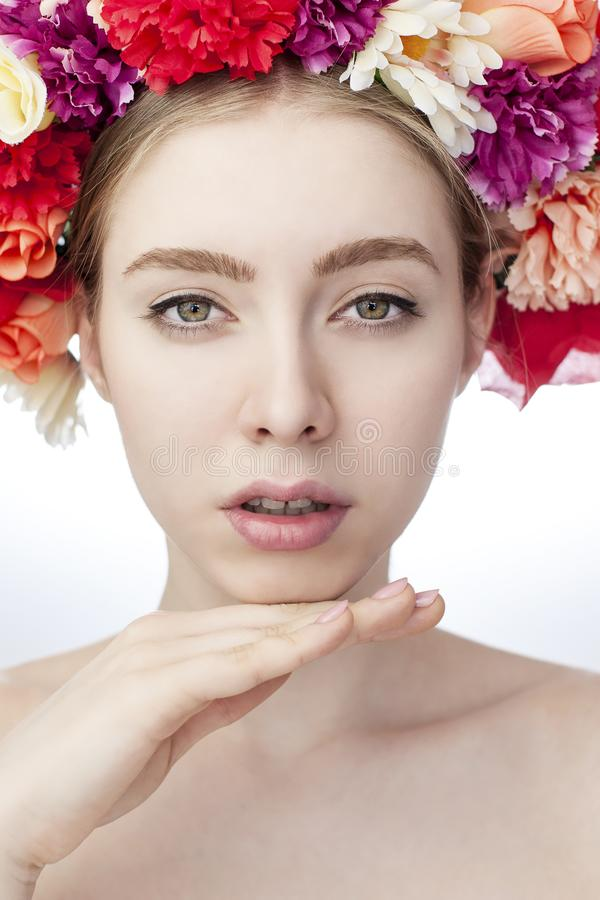 Female model with delicacy beauty. Decorative garland of colorful flowers on her head. Spring - concept stock image