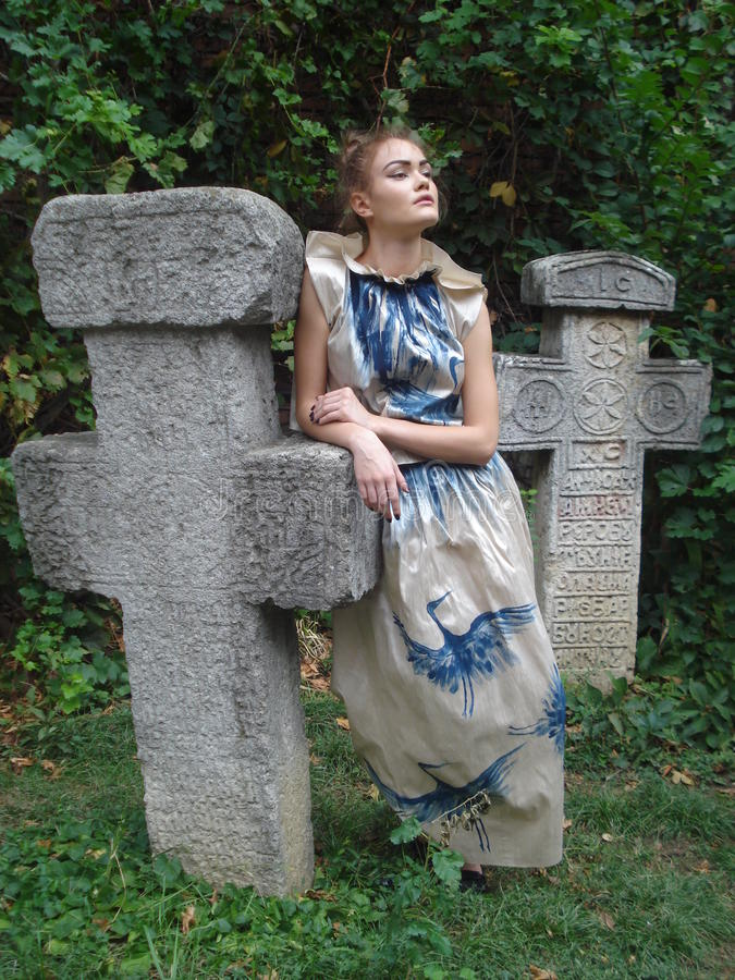 Female model leaning on traditional stone cross stock photo