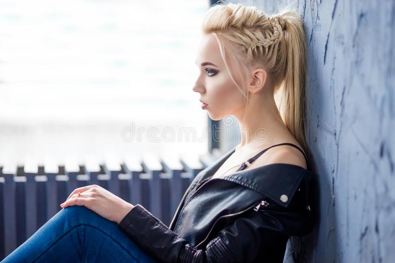 Fashion portrait of a young blonde woman in black leather jacket and blue jeans. stock photos