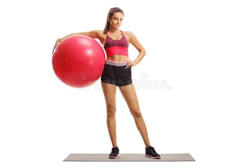 Female model posing with a fitness ball on an exercise mat royalty free stock photography