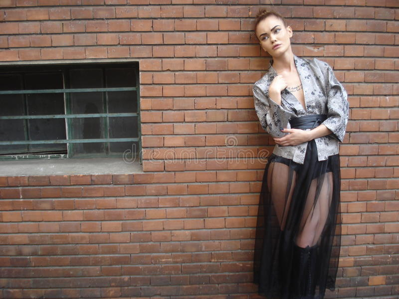 Female model posing in front of brick wall stock photography