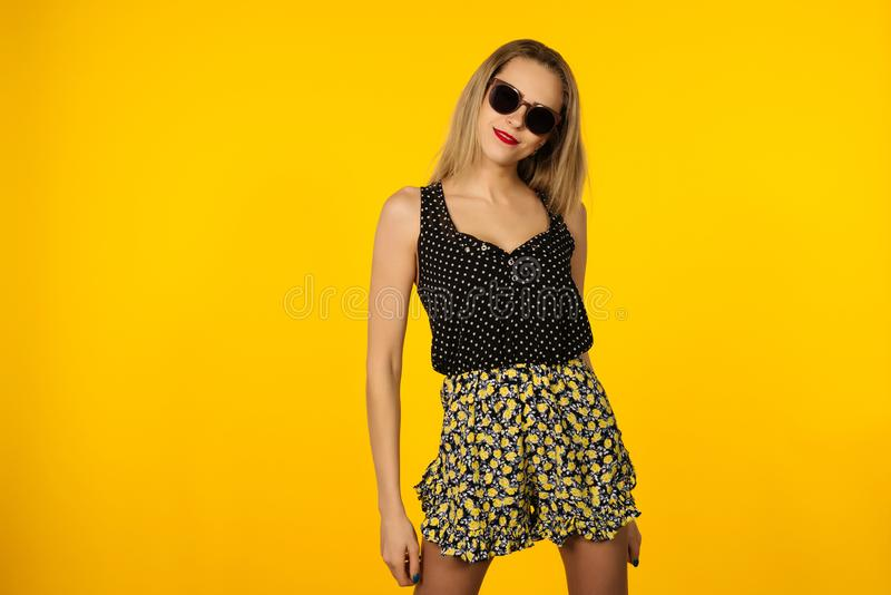 Female model posing with smile face expression on yellow background. Close-up portrait of stylish european girl standing in front royalty free stock photo