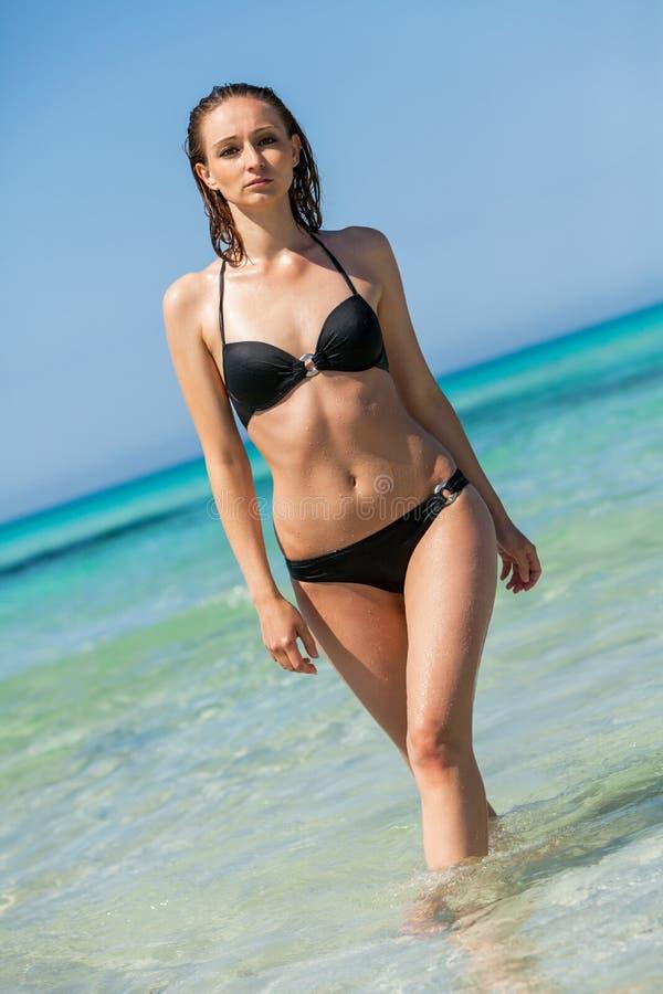 Female model wearing black bikini in the water royalty free stock photography