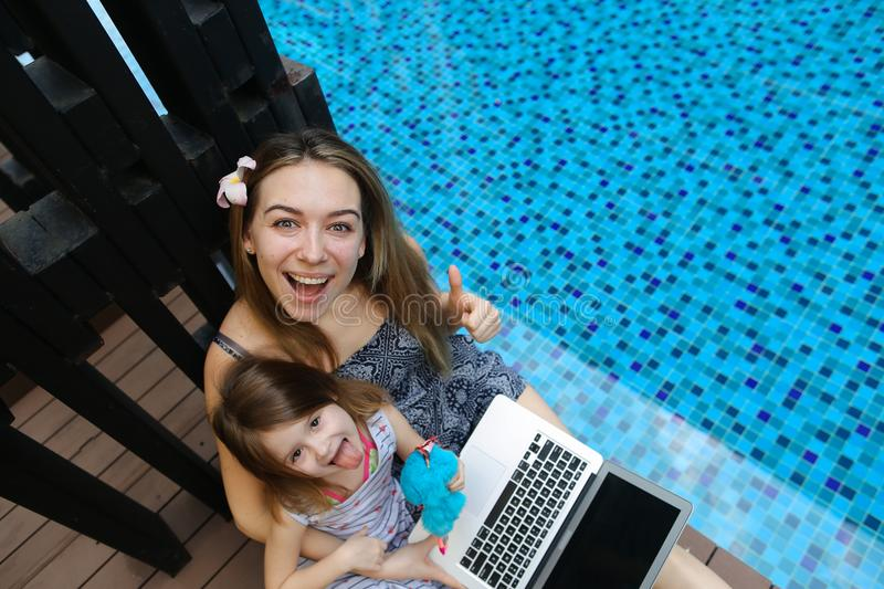 Close-up of female mother, daughter and laptop on background of swimming pool stock photos