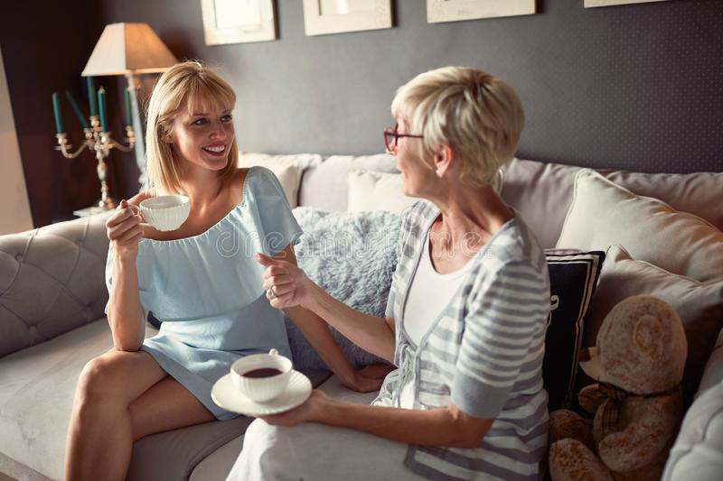 Female with mother talking and drinking coffee stock images