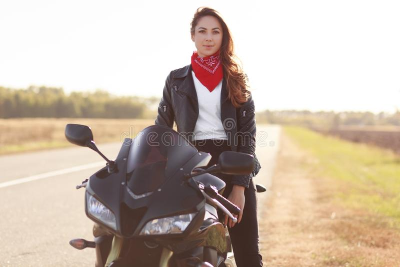 Female motocross racer dressed in black leather jacket, poses on her motorcycle, has adventure in countryside, likes risky sport,. Looks directly at camera royalty free stock images