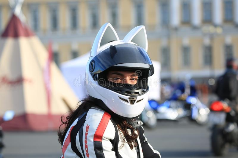 Female motorbiker in an anime cat helmet looking at the camera stock images
