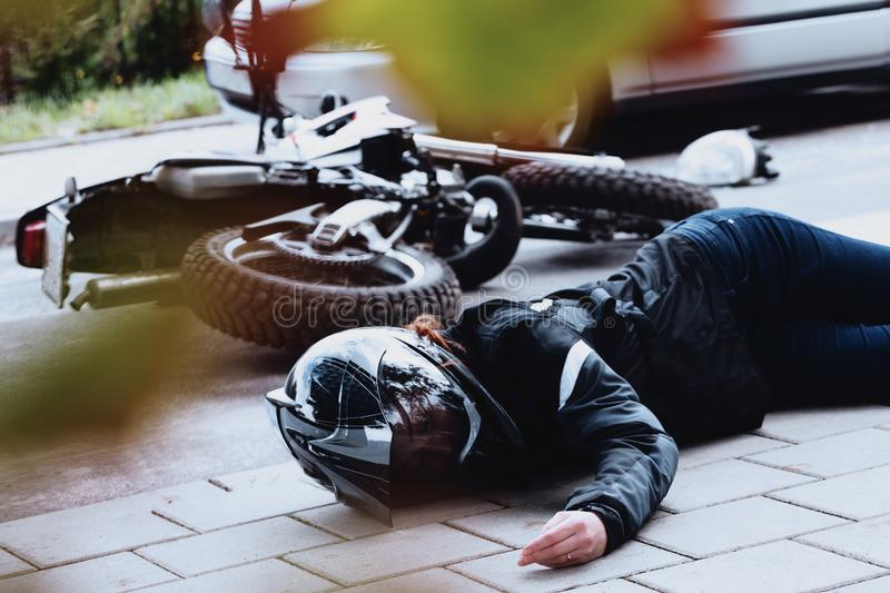 Female motorcyclist lying unconscious royalty free stock photography