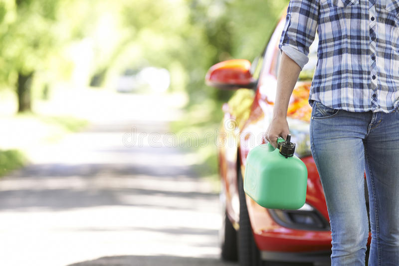 Female Motorist Carrying Fuel Can Next To Broken Down Car stock photography