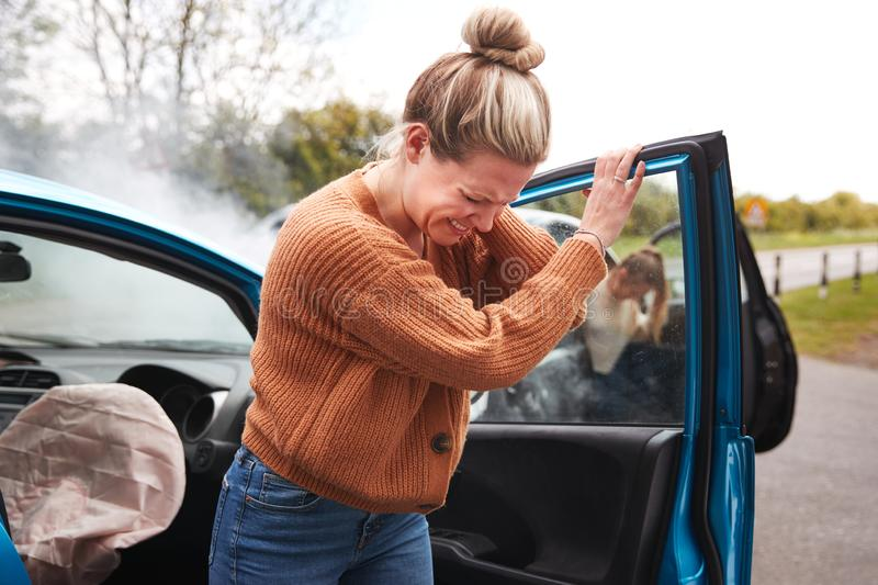 Female Motorist In Crash For Crash Insurance Fraud Getting Out Of Car royalty free stock photo