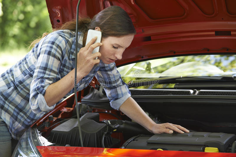 Female Motorist Phoning For Help After Breakdown royalty free stock photo