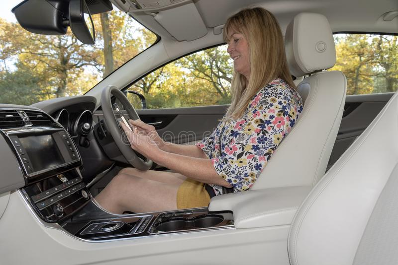 Female motorist using a mobile telephone from inside a car. Woman driver using a mobile phone from the drivers seat of a luxury car royalty free stock photography