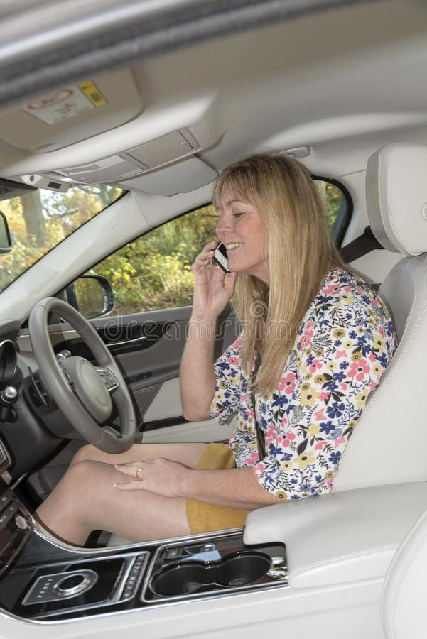 Female motorist using a mobile telephone from inside a car. Woman driver using a mobile phone from the drivers seat of a luxury car stock photography