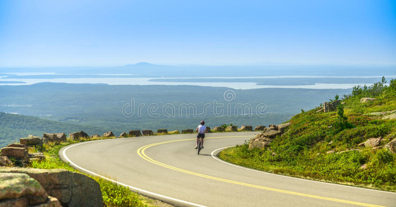 Female mountain bike cyclist riding downhill along Cadillac Mountain road in Acadia National Park stock images