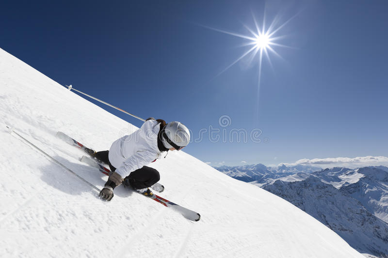 Female mountain skier. Female skier on a steep slope with mountainraing and sun in the background royalty free stock photos