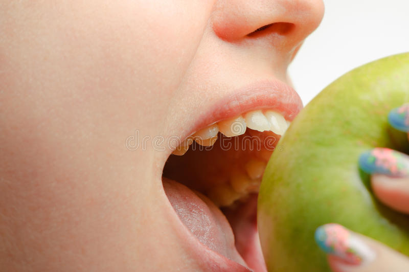 Female mouth and green apple close up. Photo of a female mouth and green apple close up royalty free stock photo