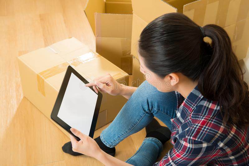Female moving new house checking on digital tablet royalty free stock photo