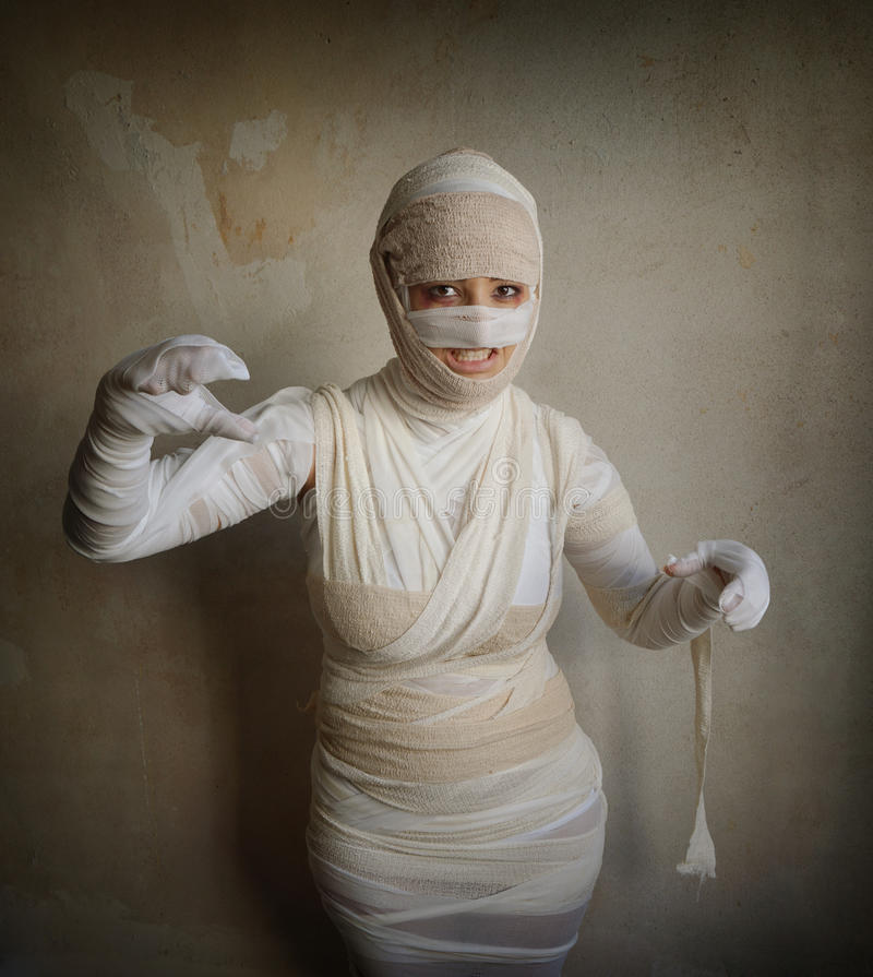 Female mummy fletching teeth. Woman wrapped in bandages as egyptian mummy halloween costume fletching teeth royalty free stock photos