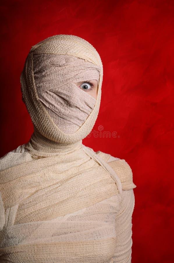 Female mummy. Wide-eyed female mummy covered in bandages royalty free stock photo