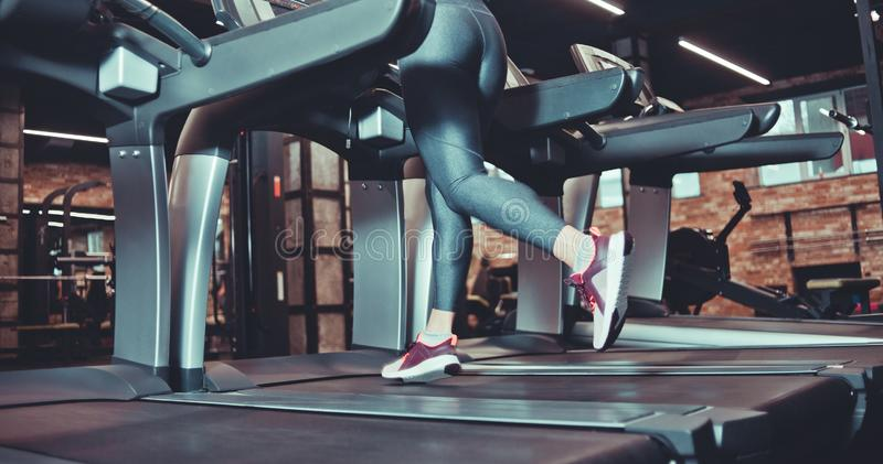 Female muscular feet in sneakers and leggins running. On the treadmil at gym. Cardio training stock photos
