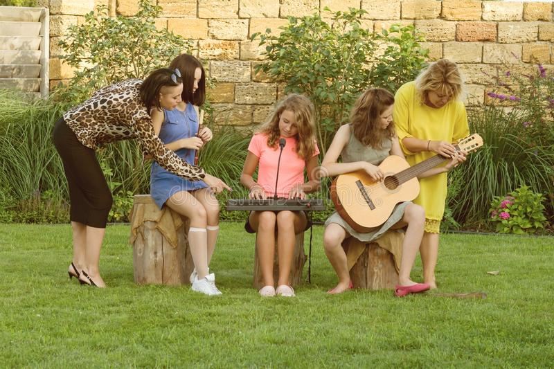 Female music teacher with pupils having music lesson outdoors. Music band of teen girls with musical instruments. Female music teacher with pupils having music royalty free stock image