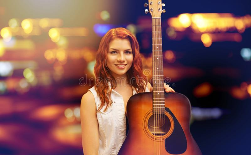 Female musician with guitar over night city lights. Music, people and musical instruments concept - female musician with acoustic guitar over night city lights stock images