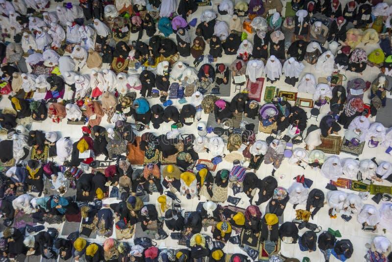 Female Muslim women wait for evening prayers facing the Kaabah in Makkah, Kingdom of Saudi Arabia. stock photos