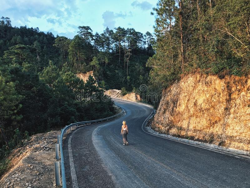 A female on a narrow curvy road stock images