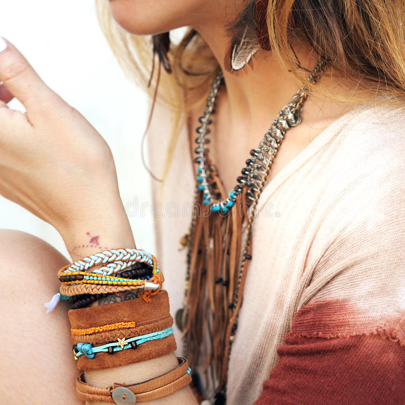 Female neck and hands with many boho bracelets, leather necklace and earrings with feathers royalty free stock photography