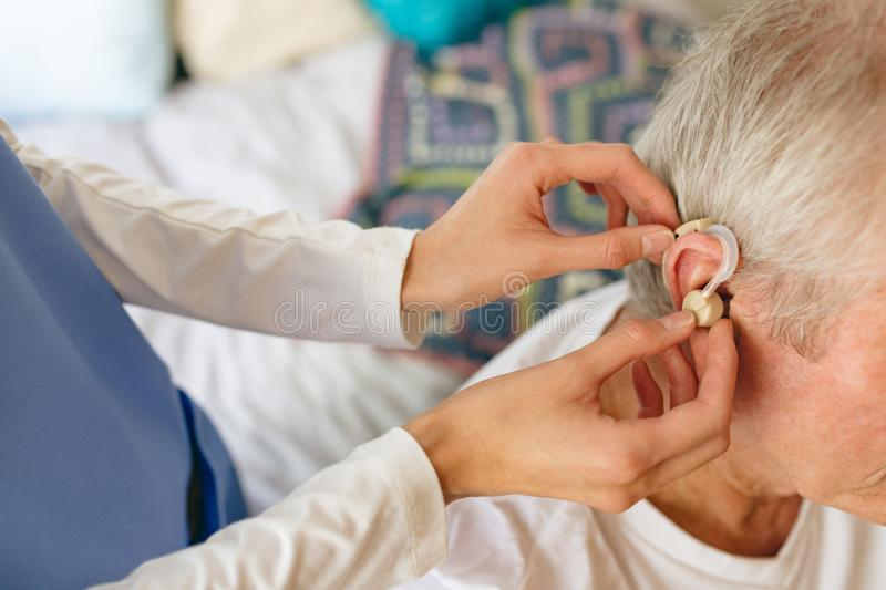 Female nurse applying hearing aid to senior male patient ear. How angle view of female nurse applying hearing aid to senior Caucasian male patient ear at stock image