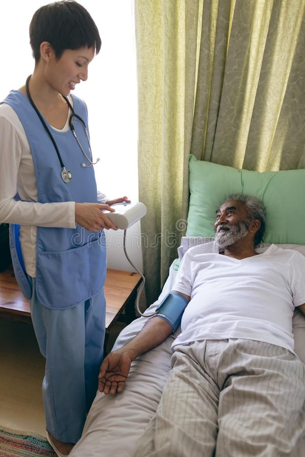 Female nurse checking blood pressure of senior male patient stock photos