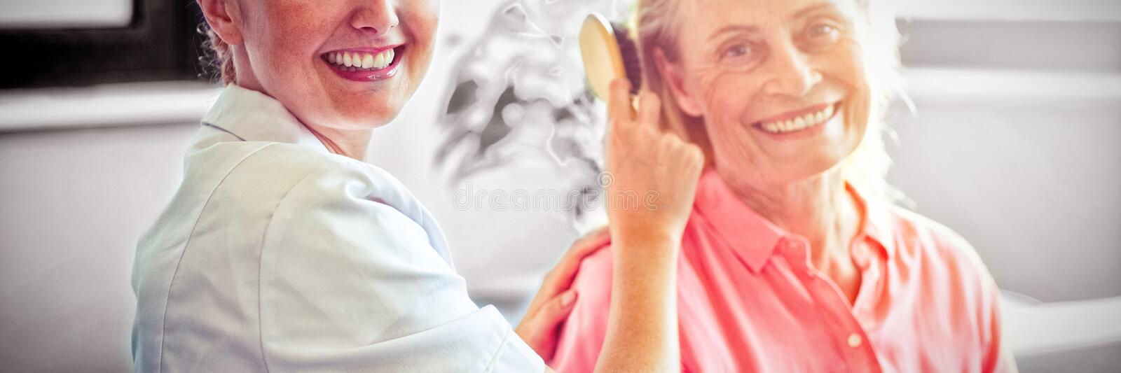 Female nurse combing hair of senior woman stock images