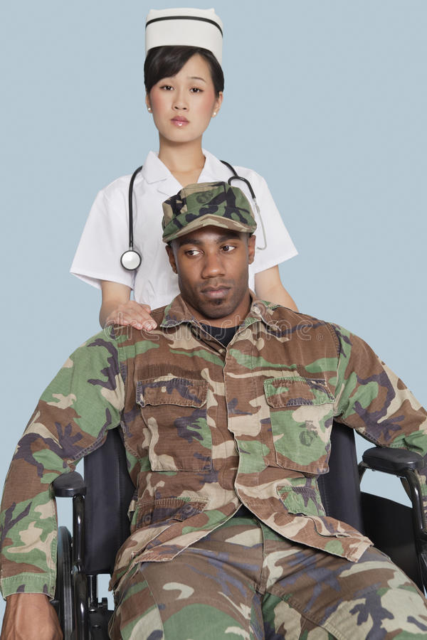 Female nurse comforting disabled US Marine Corps soldier in wheelchair over light blue background stock photography