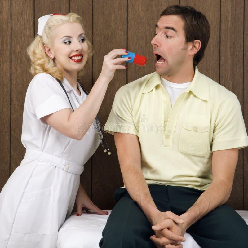 Female Nurse Giving Man Giant Pill. Stock Photo