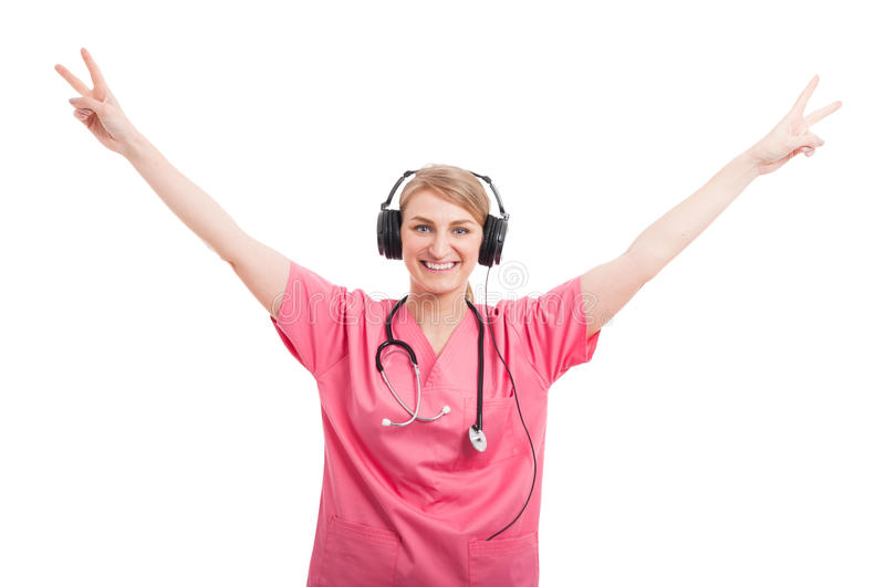 Female nurse with headset on showing double victory. Sign and smiling isolated on white background stock image
