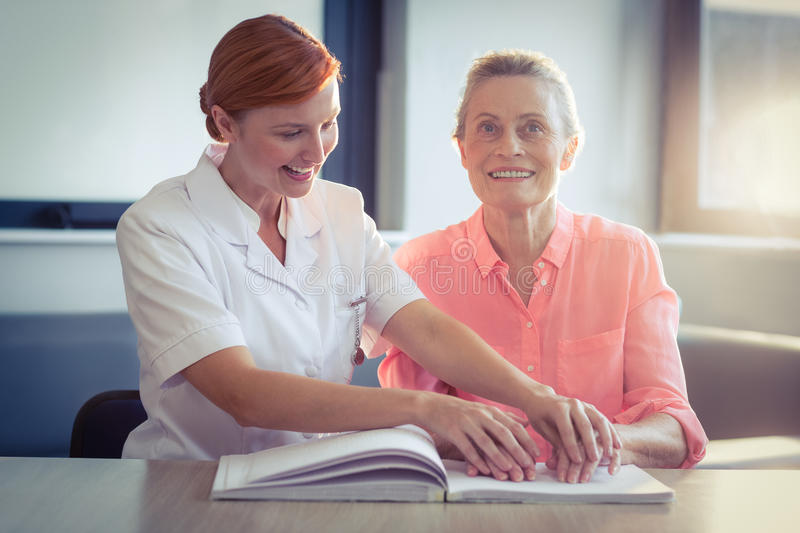 Female nurse helping patient in reading the braille book. At home stock photography