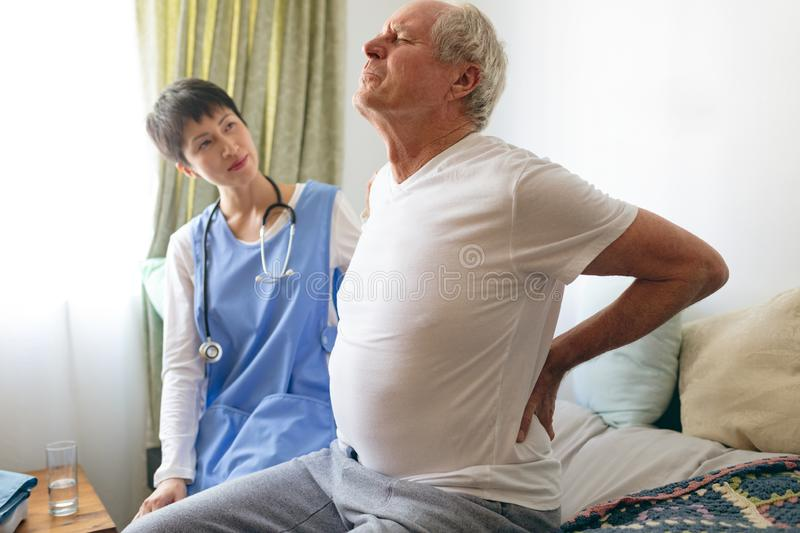 Female nurse helping senior male patient with back pain. Side view of Asian female nurse helping senior Caucasian male patient for back pain at retirement home royalty free stock image