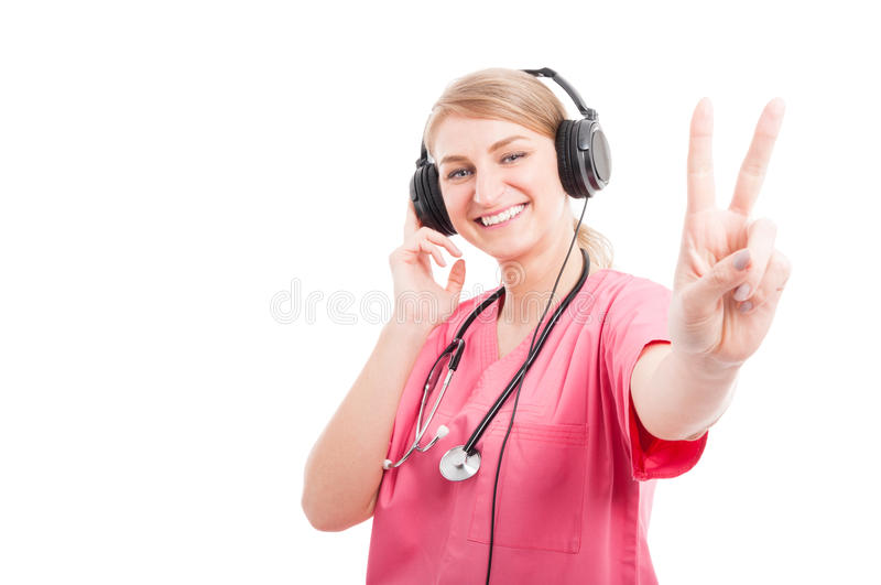 Female nurse listening to headset showing peace. Gesture isolated on white background with copy text space stock photography