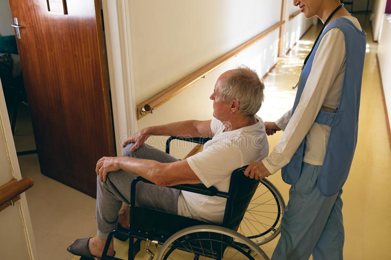 Female nurse pushing disabled senior male patient sitting in wheelchair stock photography