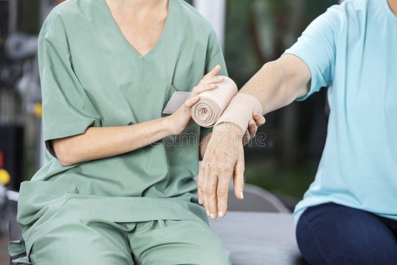 Female Nurse Putting Crepe Bandage On Senior Woman's Hand. Midsection of female nurse putting crepe bandage on senior woman's hand at rehab center royalty free stock photos