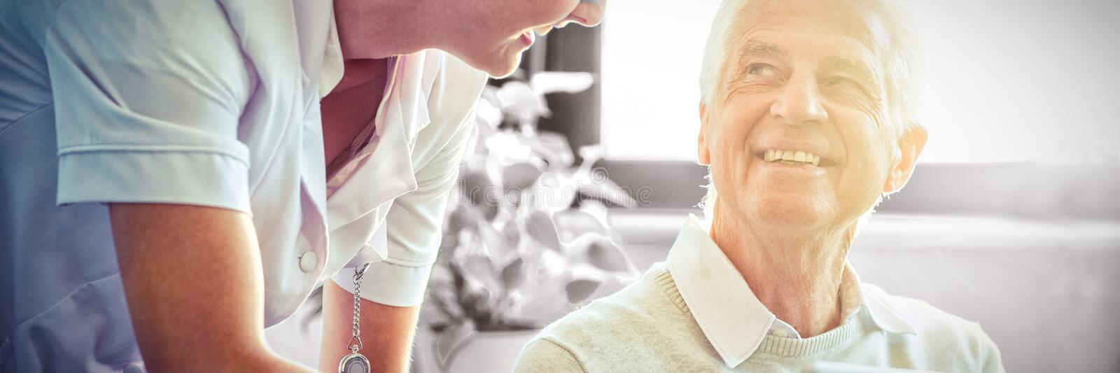 Female nurse showing medical report to senior man on digital tablet royalty free stock photos