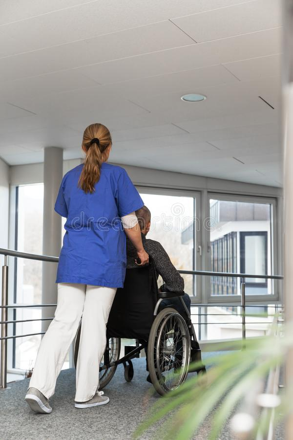 Female nurse is sliding a man in a wheelchair stock photo